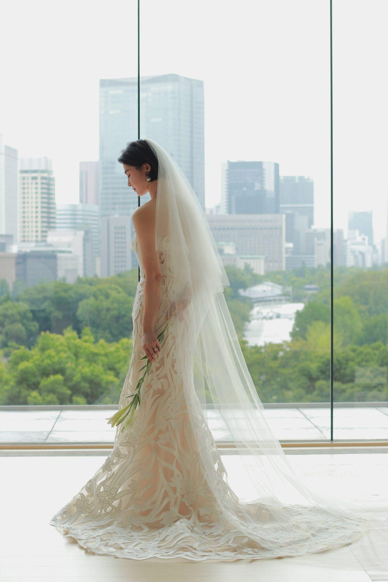 皇居と丸の内のビル群を目の前にしたパレスホテル東京のチャペルに総レースのマーメイドラインのウェディングドレスがマッチします