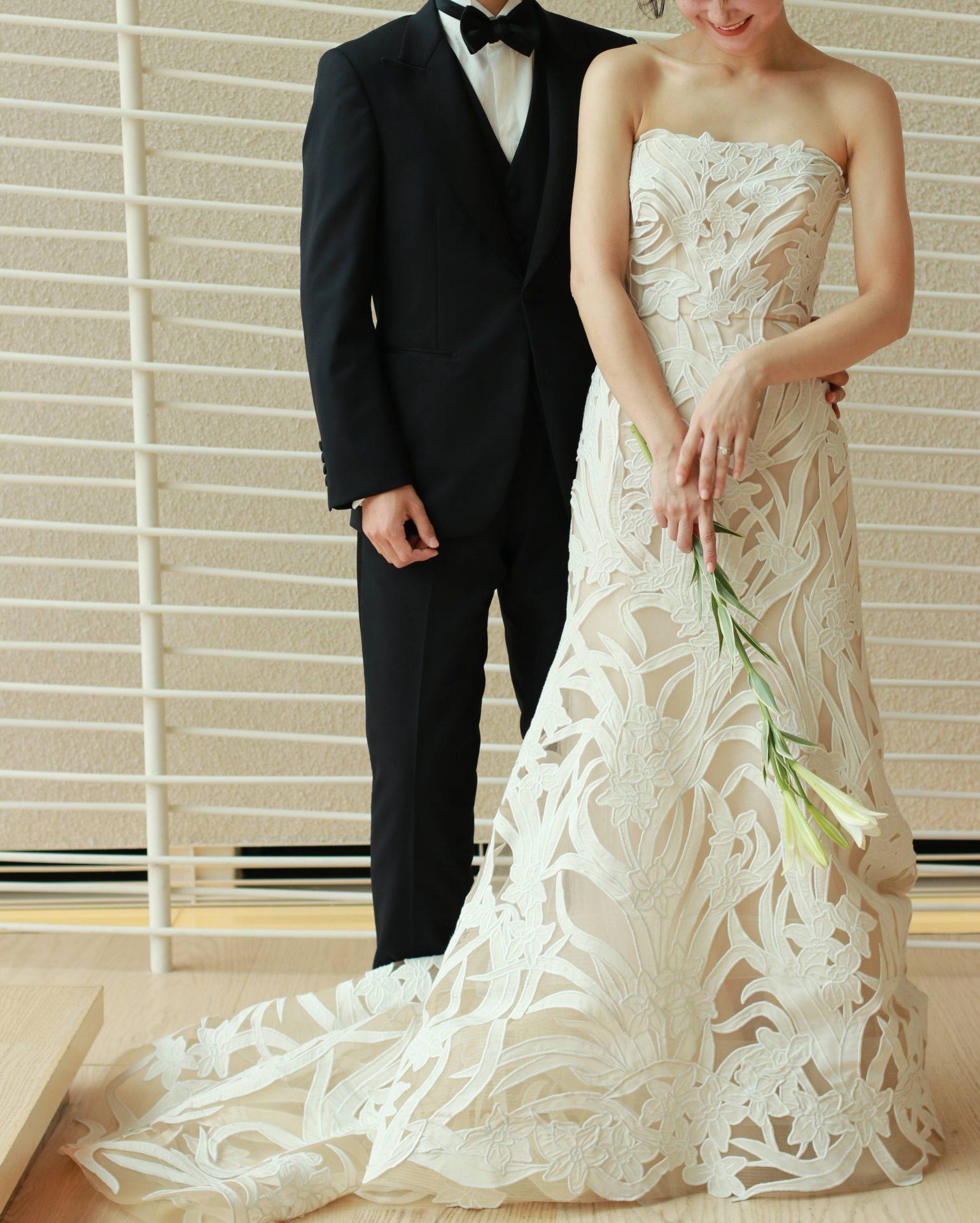結婚式当日の新郎新婦が横に並んだ時、シンプルなブラックのタキシードと華やかな総レースのウェディングドレスがお互いを引き立てあいます