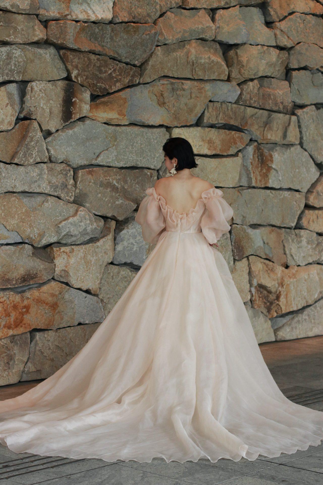 ロングトレーンのウェディングドレスはクラシックな印象になりますが、オフショルダーデザインと合わさる事でモダンなバックスタイルを叶えます