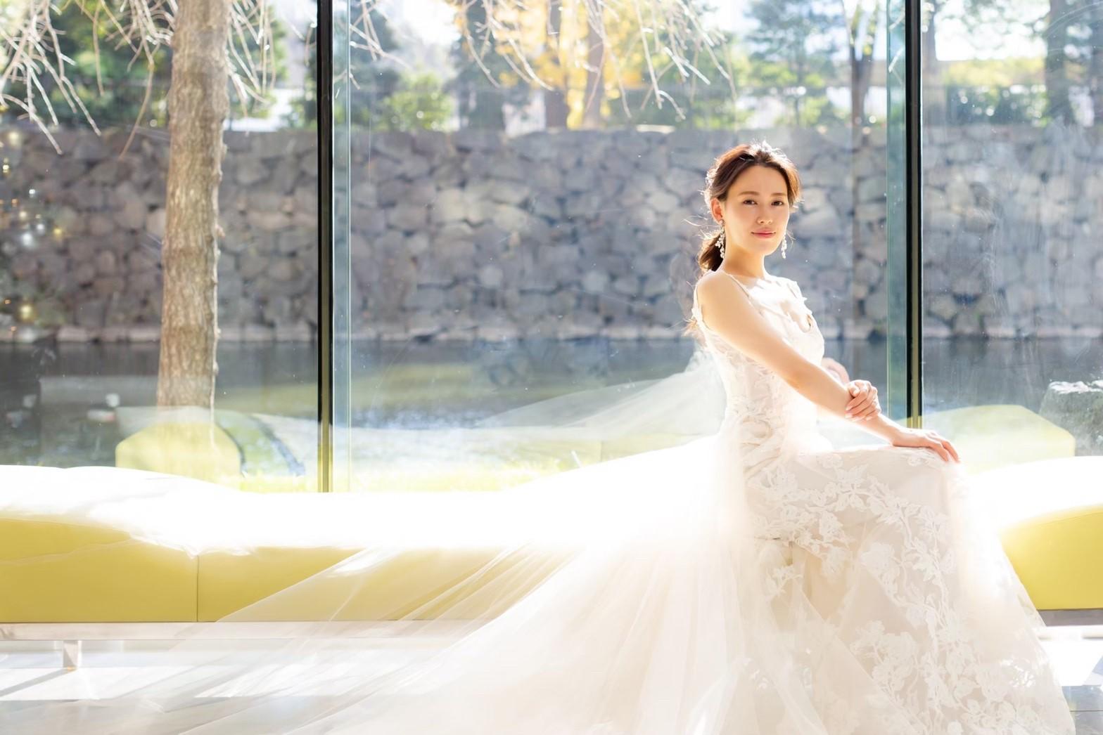 日本の花嫁に大人気のMonique Lhuillierの総レースのマーメイドラインにチュールトレーンがついた2Wayタイプのウェディングドレスが華やかな印象を与えます